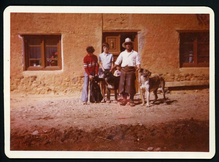 Efigenio Domínguez con su hijo, un sobrino, dos mastinas y un perro de aqueda en la puerta de su casa en Cerezales del Condado