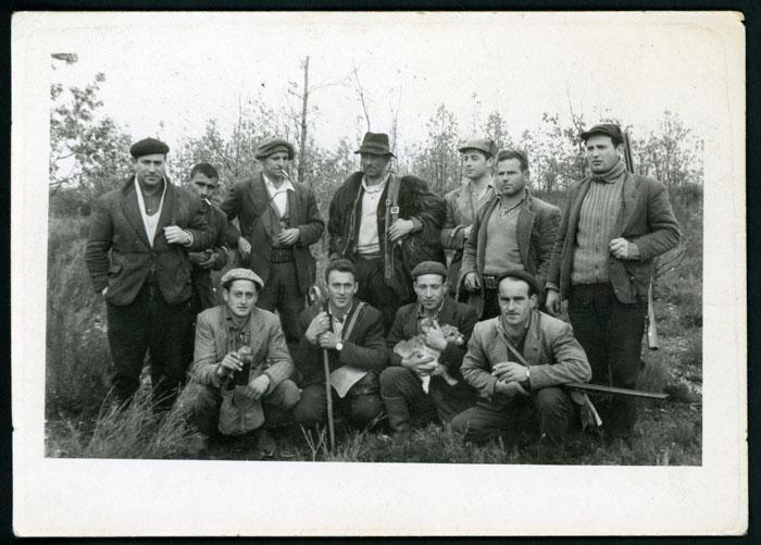 Emérito Robles de pastor junto a un grupo de cazadores en el monte.