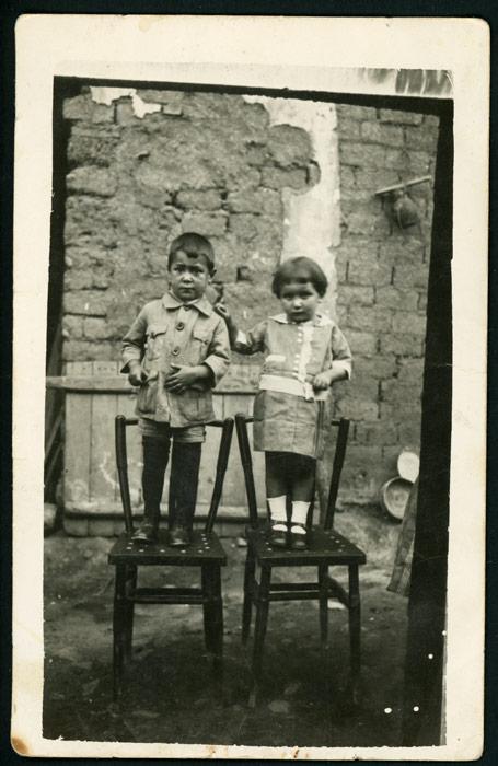 Retrato de los hermanos Juliana y Germán subidos en sillas