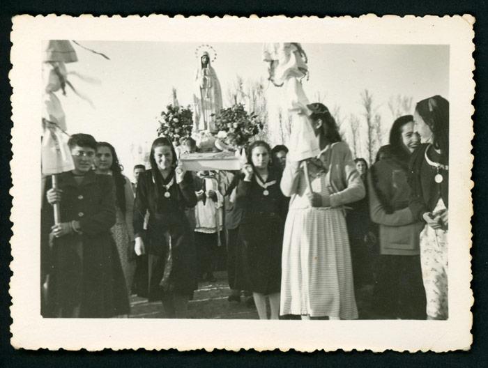 Grupo de chicas llevando en andas a la Virgen de Fátima en una procesión en Barrillos de Curueño