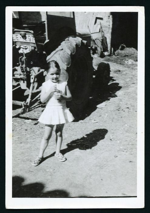 Maite González posado delante de un tractor en el corral de la casa familiar de Barrillos de Curueño