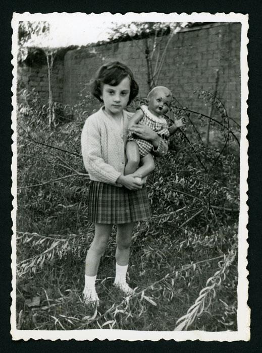 Mari Carmen posando con una muñeca en una huerta en Barrillos de Curueño