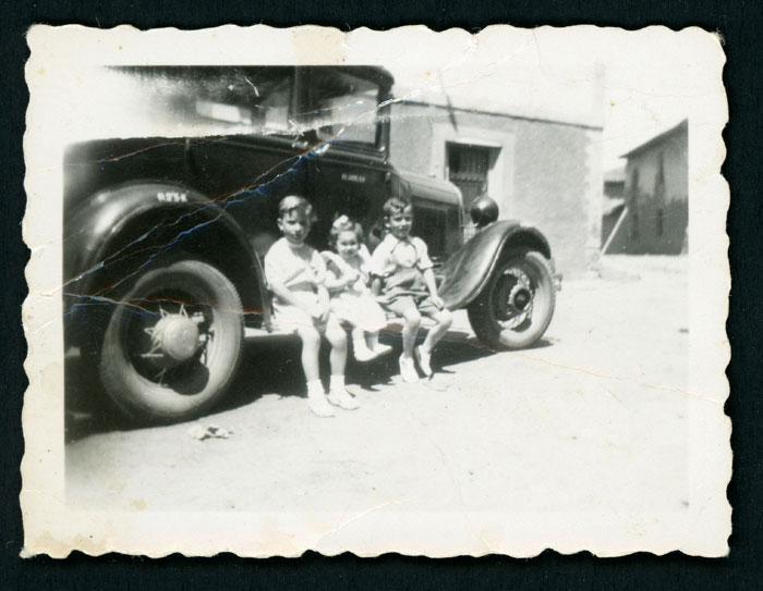 Tres niños sentados en un coche en Barrio de Nuestra Señora
