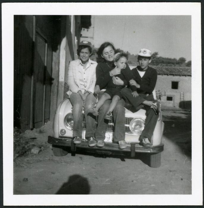 Alberto José González, Marigel González y Mari Carmen sentados en el capó de un coche en Cerezales del Condado