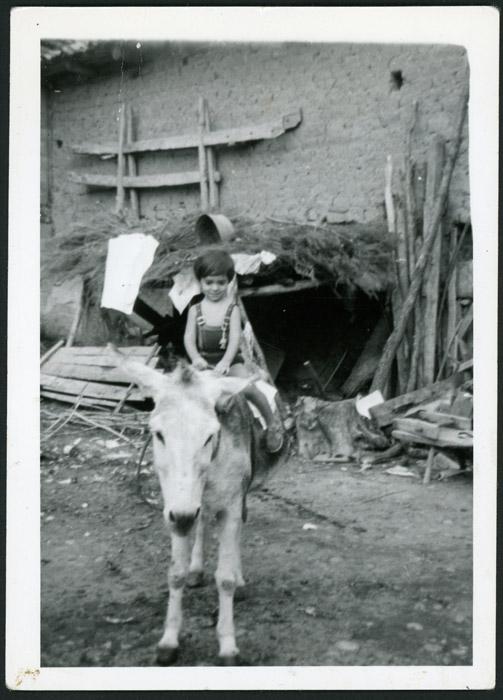 Óscar García subido en la burra en la casa de su abuelo en el patio de la casa familiar de Cerezales del Condado
