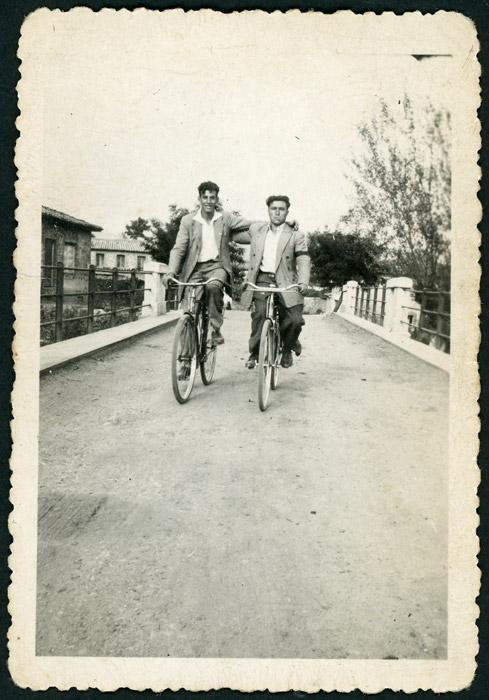Dos mozos en bicicleta en el puente que une Ambasaguas de Curueño y Barrio de Nuestra Señora