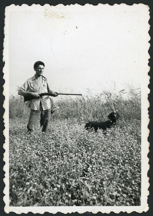 Saturnino González en el campo con escopeta y perro posando como un cazador