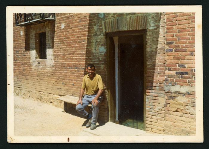 Tino González sentado en la puerta de la casa familiar en Cerezales del Condado.
