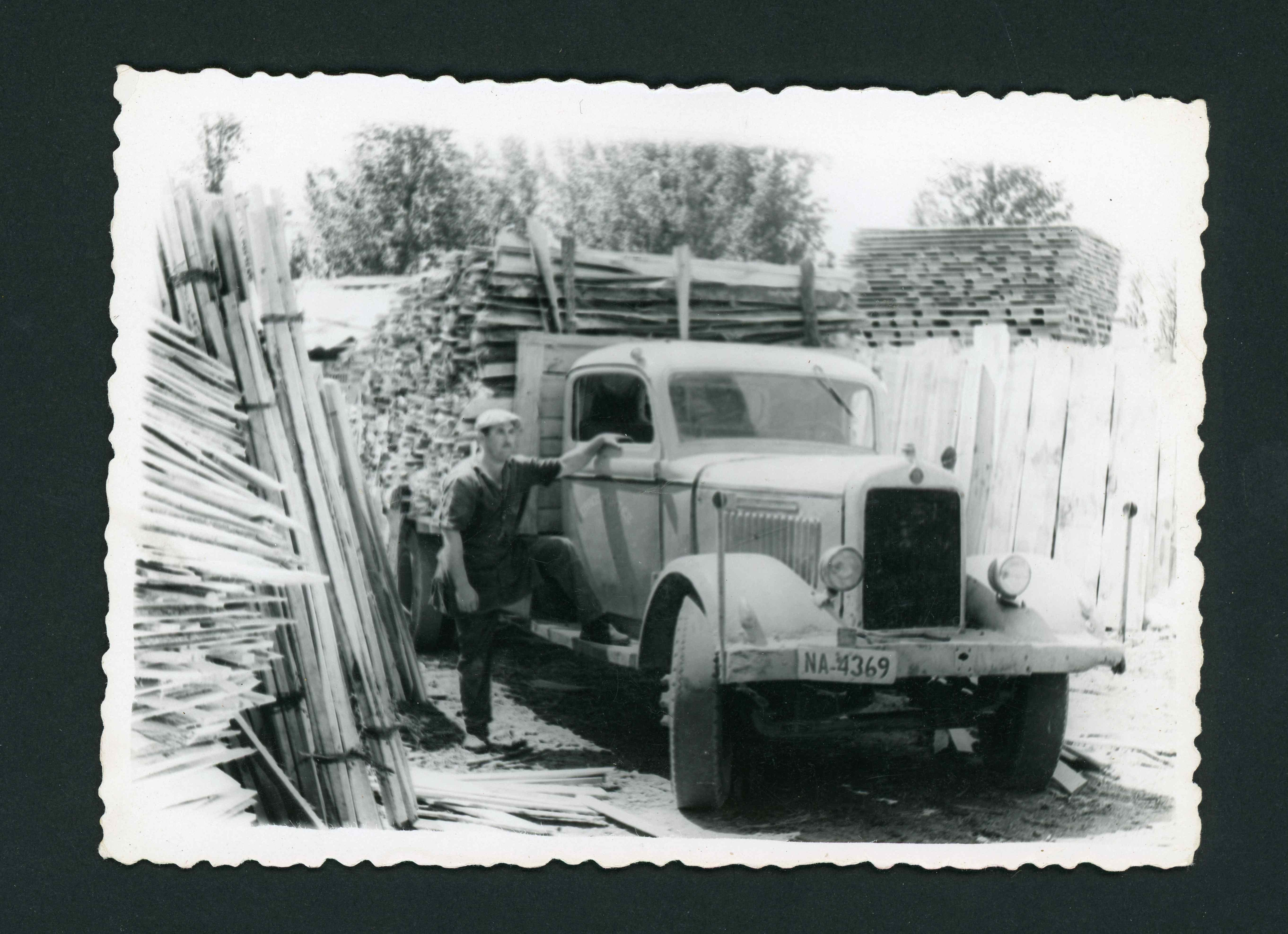 Arsenio Ferreras con el camión GMC cargado con rachos en el aserradero de Barrio de Nuestra Señora