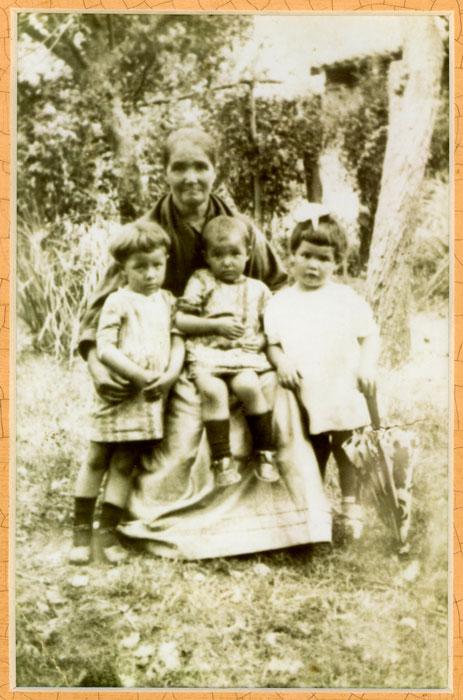 Cecilia Arroyo con sus tres nietas mayores en la huerta de la casa familiar de Barrillos de Curueño