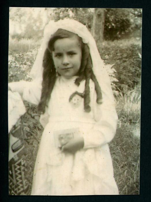 Inés López de primera comunión en la huerta de la casa familiar en Barrillos de Curueño.
