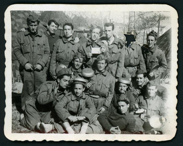 Grupo de militares posando, uno de ellos con la cara recortada.