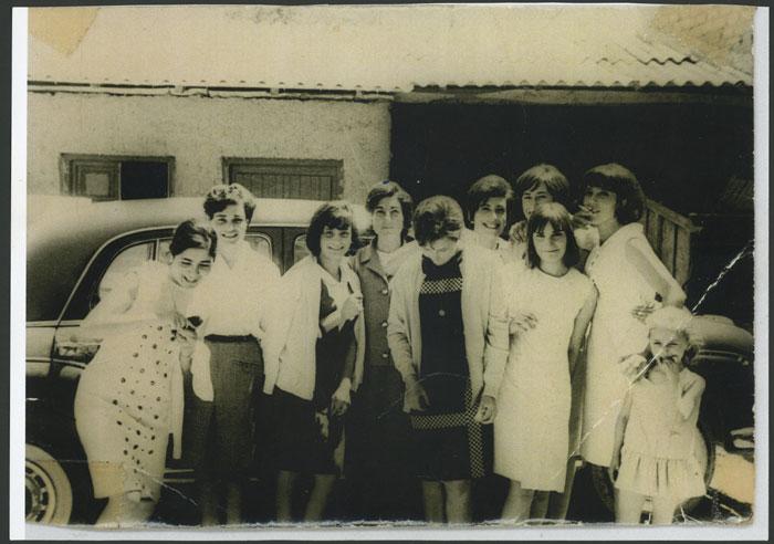 Grupo de chicas arregladas posando delante de un coche en Devesa de Curueño