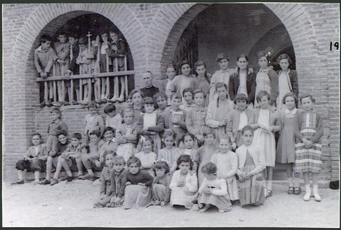 El cura don Amancio con las niñas y niños de Devesa de Curueño en la puerta de la iglesia.