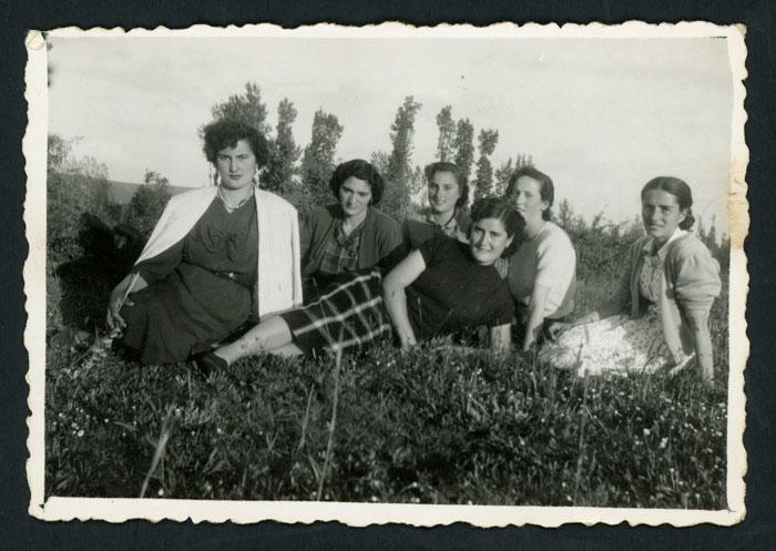 Grupo de mujeres jóvenes sentadas en la pradera en el soto de Devesa de Curueño