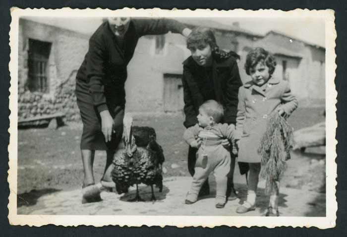 Celestina González, Marisa Fernández, Luisa Robles y Manolo Villaverde en un pontón con un pavo el día de Navidad en Devesa de Curueño