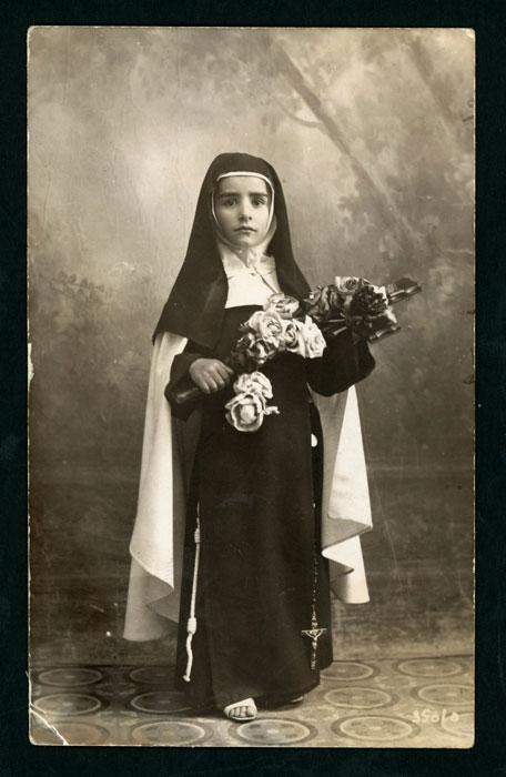 Recordatorio de primera comunión de Angelina Fernández vestida con el hábito de Santa Teresa en un estudio de León