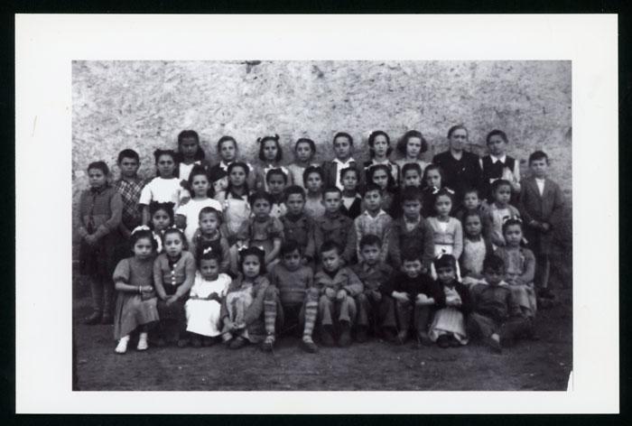 La maestra Marina Liébana con las alumnas y alumnos en el exterior de la escuela de Devesa de Curueño