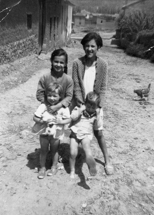 Pilar y Gelines Robles con unos primos delante de la casa familiar en Barrillos de Curueño