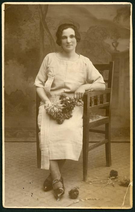 Retrato de estudio de una mujer sentada con un ramo en la mano.