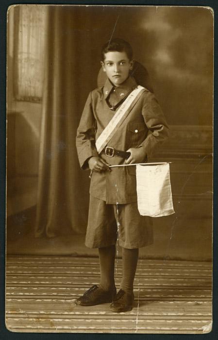 Retrato de estudio de un niño con uniforme y banderín en Argentina