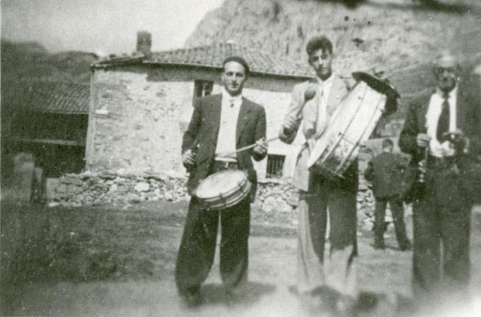 El tío Gildo de la Varga con la dulzaina, su hijo Marceliano tocando el tambor y un joven tocando el bombo en un pueblo de la montaña.