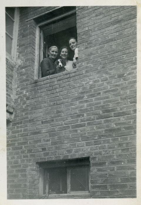 La abuela Antolina de Cabo, Avelina González y Felisa Gutiérrez con un perro en una ventana de la casa familiar en Cerezales del Condado