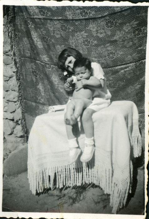 Felisa Gutiérrez con su hermano Tino en brazos en el corral de la casa familiar en Cerezales del Condado