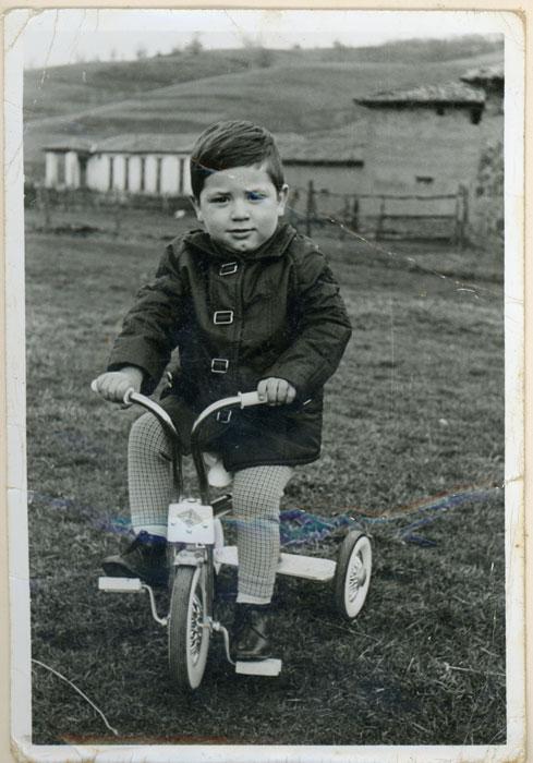 Roberto Fernández en un triciclo en la era de Cerezales del Condado