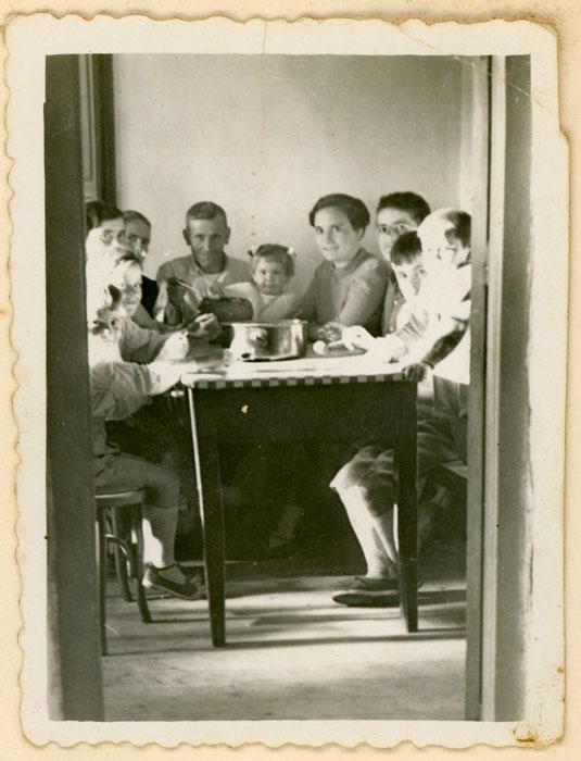 Familia sentada alrededor de la cazuela en Cerezales del Condado