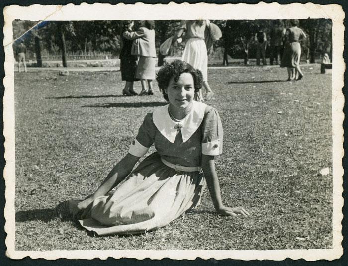 Rubenita Aller sentada en una pradera en una fiesta