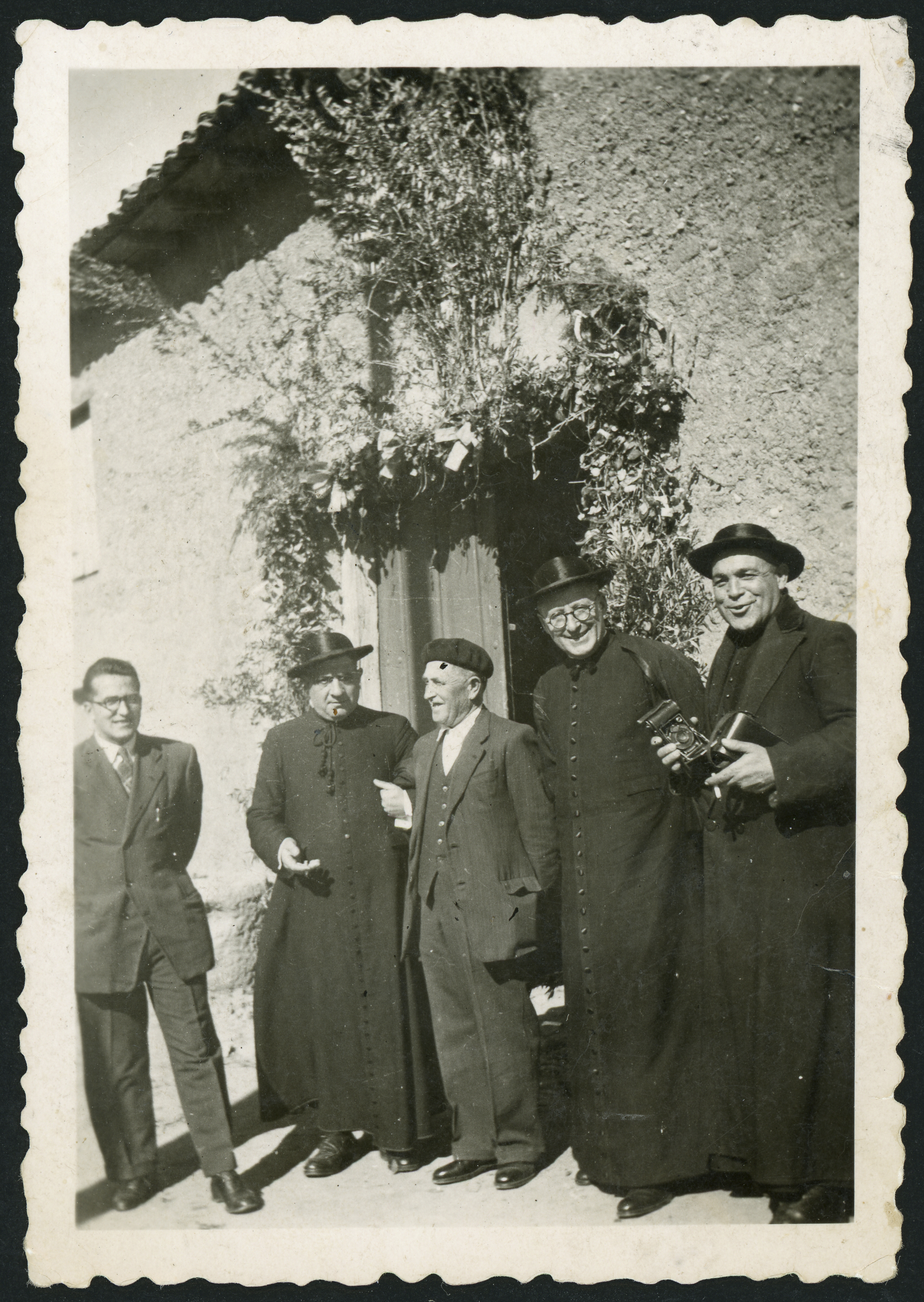 Don Anselmo con una cámara de fotos junto a otros sacerdotes en la puerta de la casa rectoral en Cerezales del Condado