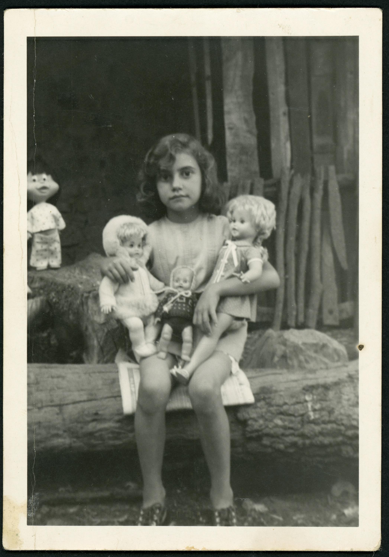 Mª del Mar Martínez con dos muñecas en el taller de carrero de su abuelo en Ambasaguas de Curueño