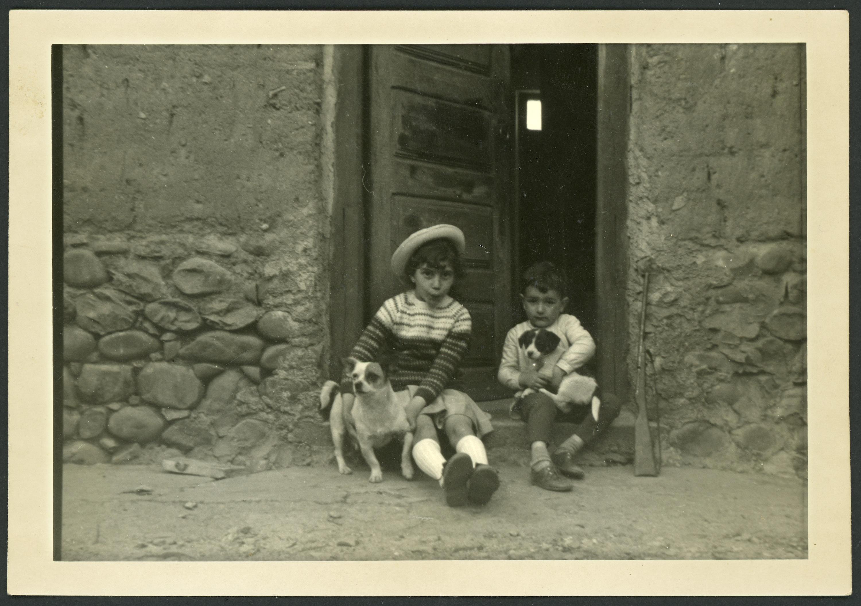Mª del Mar Martínez y un amigo con dos perros en la puerta de la casa familiar de Ambasaguas de Curueño