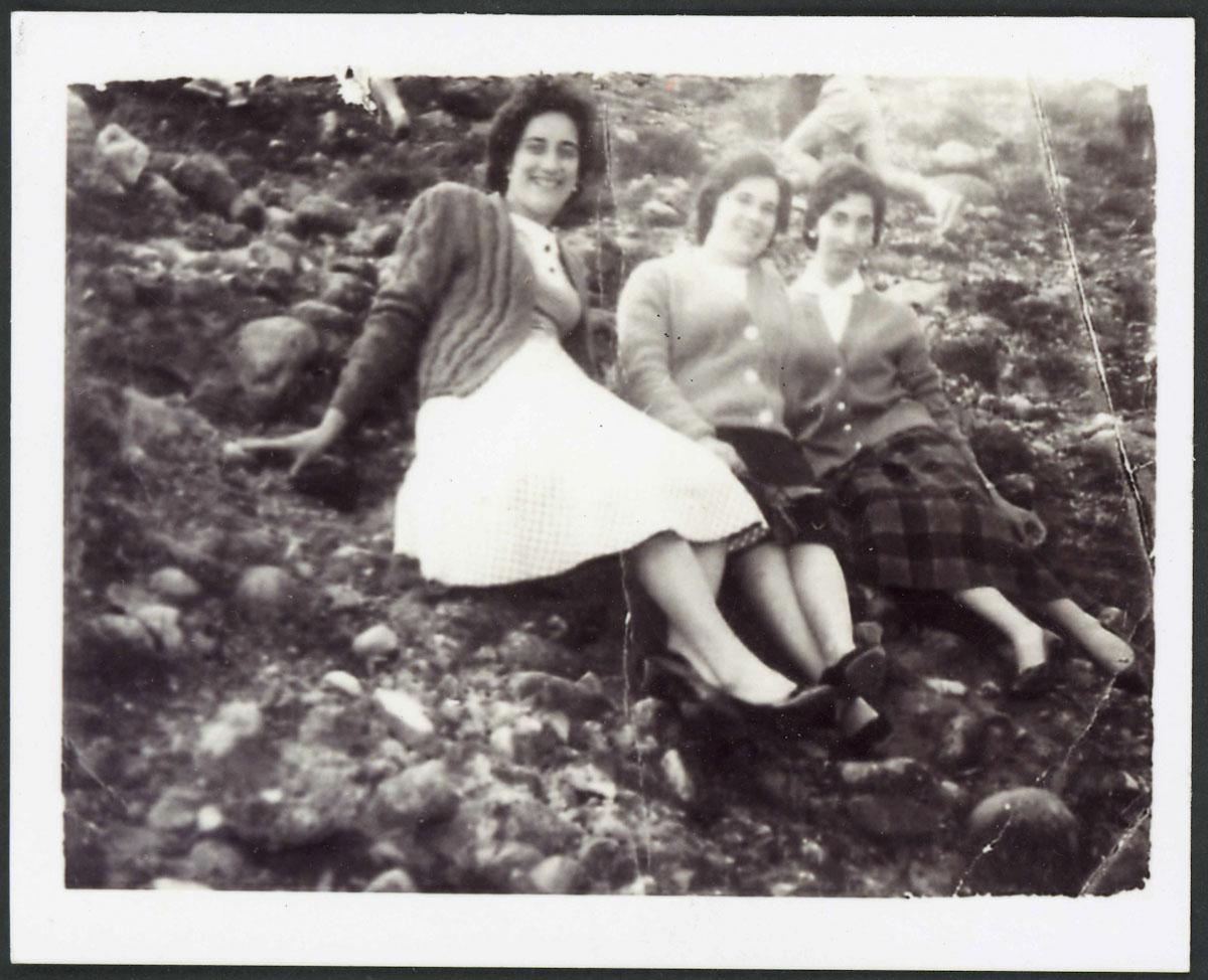Tres chicas de Lugán sentadas en unas peñas