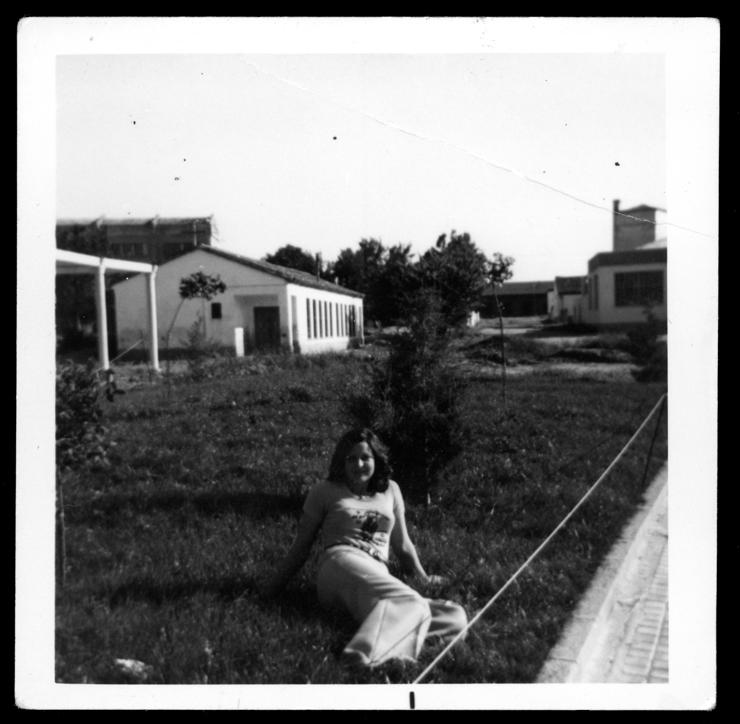 Joaquina Sánchez sentada en la hierba delante de las antiguas escuelas en Peñaranda de Bracamonte