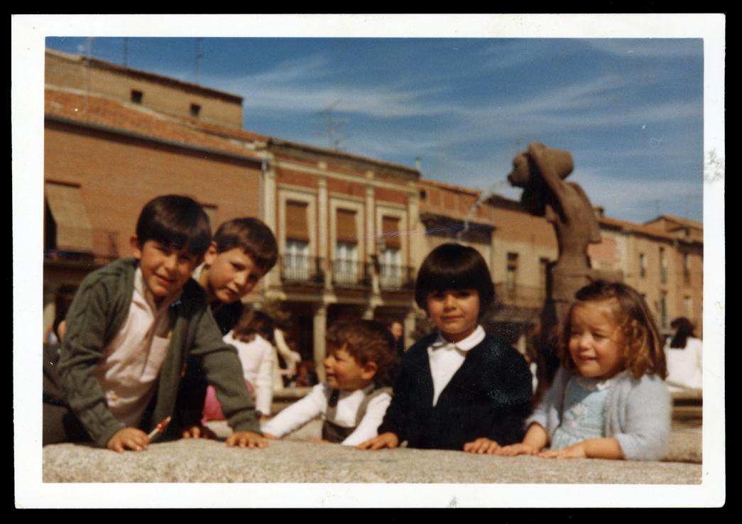 Niños posando delante de la fuente del hombre con cántaro en la Plaza España